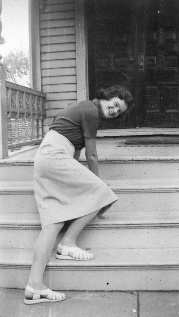 Virginia standing on a porch bent over with her hands on the steps looking back.