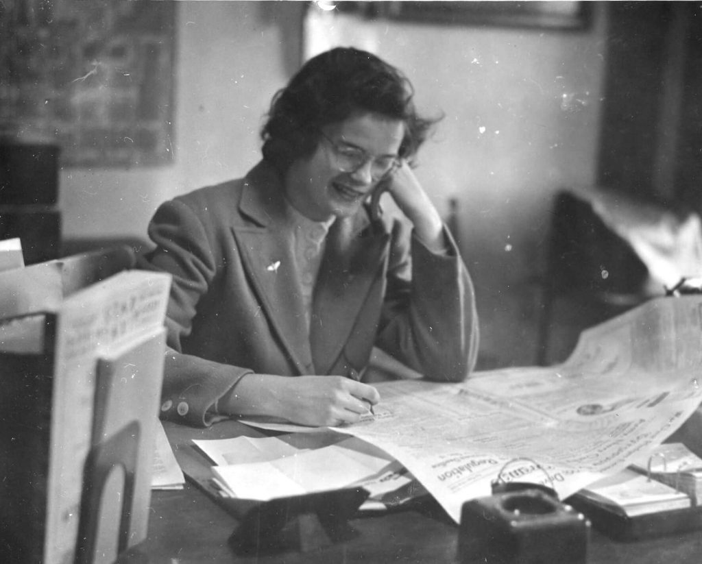 Virginia sitting at a desk reading the news paper.